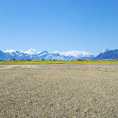 empty rural road near snow mountains in fine day in new zealand