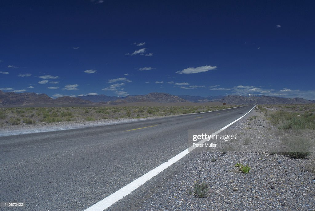 Empty rural road under cloudy sky