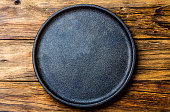 Empty rustic black cast iron plate over old wooden background. Top view