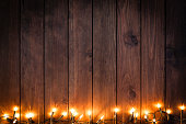 Top view of an empty rustic wooden table with Christmas lights string arranged at the bottom border making a frame and leaving useful copy space for text and/or logo. Predominant colors are brown and