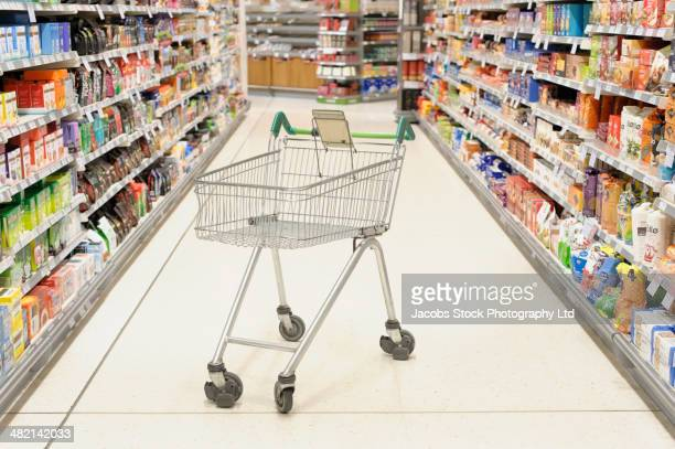 Empty shopping cart in supermarket aisle
