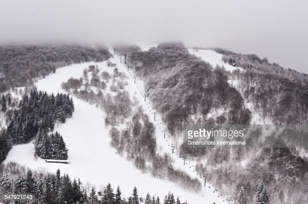Empty ski run and ski lift in winter season, Italy