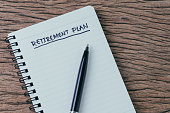 Empty small notepad with pen and handwriting headline as Retirement Plan on wood table in soft vintage tone, planning for saving and investment for the future.
