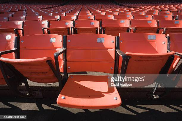 Empty stadium seats, one seat down