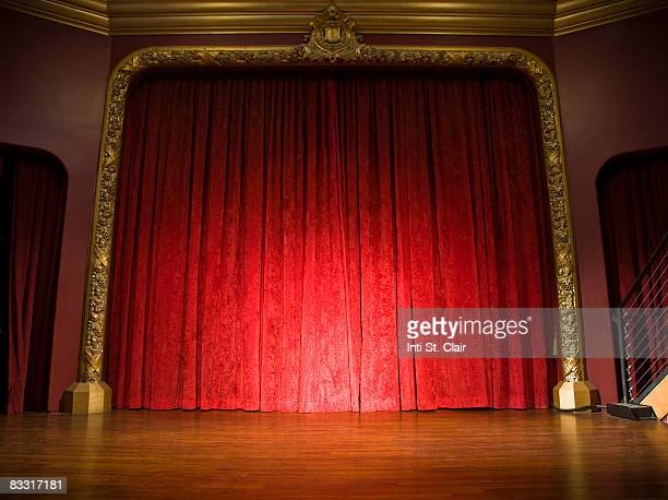 Empty stage with curtains closed and spotlight on