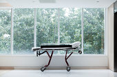 Empty stretcher in a hospital by glass windows, no people