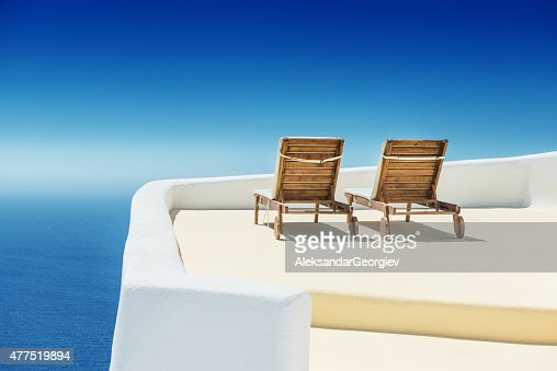 Empty Sun Lounge Chair on balcony In Santorini at Sunrise