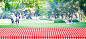 Empty table cover with red tablecloth over blur park with people background, for product display montage background, banner