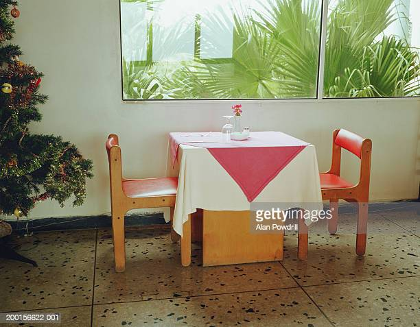 Empty table with one place setting, by window