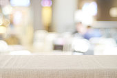 Empty tabletop with linen tablecloth over blurred cafe with bokeh background, copy space for food and product display montage background