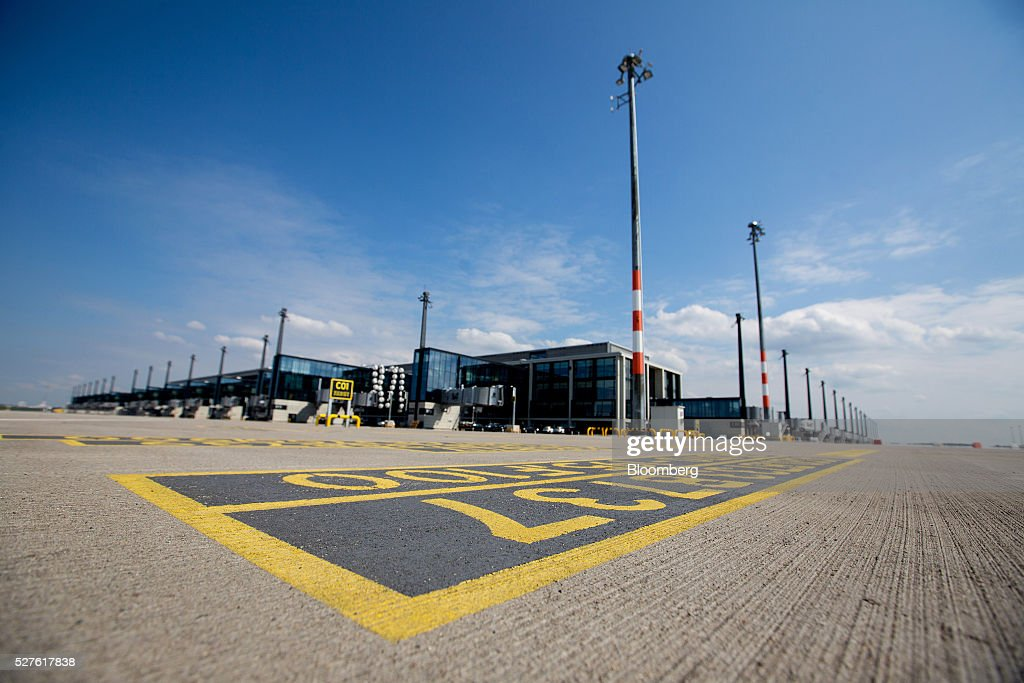 Empty tarmac sits outside a terminal building as construction work continues at Berlin Brandenburg International Willy Brandt Airport in Schoenefeld, Germany, on Monday, May 3, 2016. The massively overbudget airport was planned to open in 2010 and handle 27 million passengers a year, crowning Berlin as the continent's 21st century crossroads. Photographer: Krisztian Bocsi/Bloomberg via Getty Images
