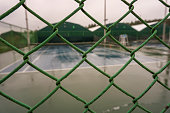 Empty tennis court behind fences on a rainy day, green fences in focus.