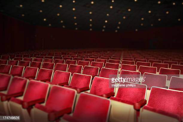 Empty Theater with Rows of Red Seats and Ceiling Lights