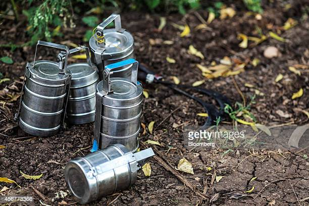Empty tiffin boxes sit next to sickles during a banana harvest in a field in Bhusawal Maharashtra India on Saturday Oct 4 2014 More than 75 percent...