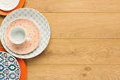 Set of empty colorful vintage plates and black coffee cup, top view on natural wood. Table setting and tableware concept