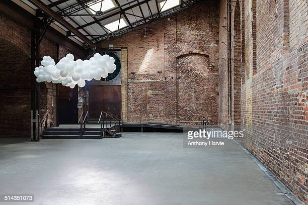 Empty warehouse with cloud made of balloons