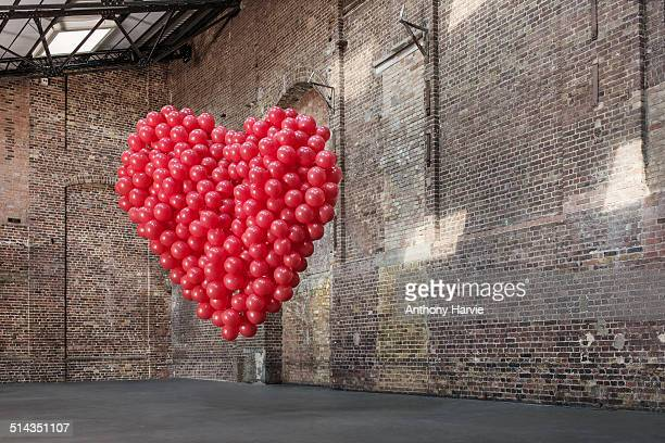Empty warehouse with red heart made of balloons