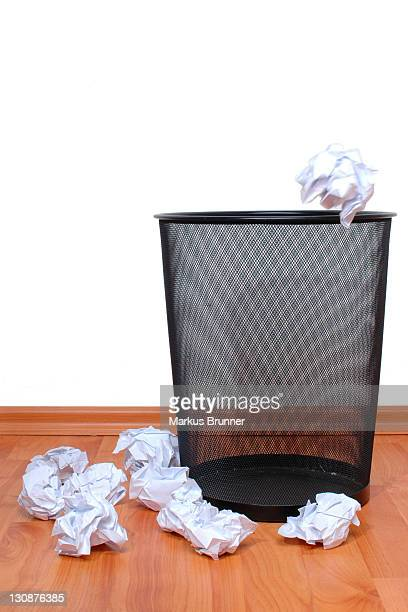 Empty wastepaper basket with lots of crumpled pieces of paper beside it