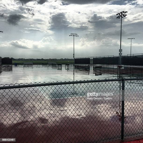 Empty Wet Tennis Court Against Sky During Monsoon