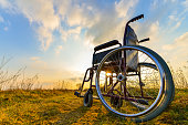 Empty wheelchair on the meadow at sunset. Miracle concept. Healed person raised and went away