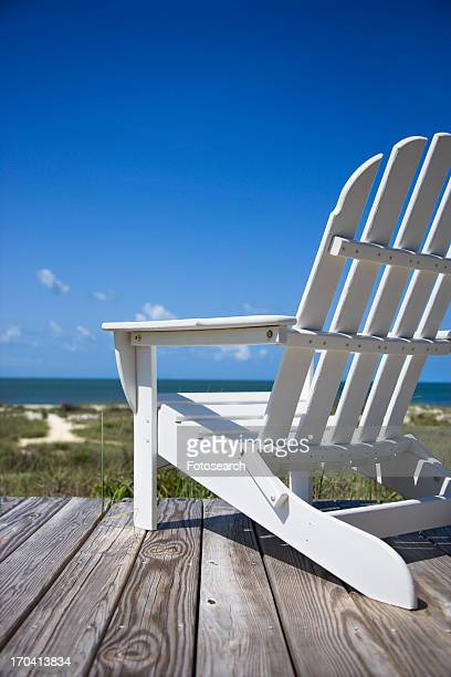 Empty white adirondack chair on wooden deck facing beach