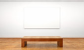 Empty customizable blank canvas hanging on a wall inside a private space or museum gallery, with a wooden bench in front of it. Bright illumination with white walls and brown parquet floor. Unframed c