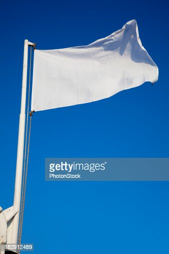 Empty white flag waves in front of deep blue sky