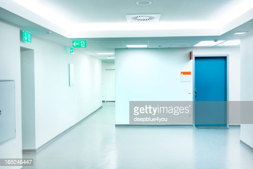 Empty white Hospital corridor with a blue door