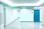 Empty white Hospital corridor with a blue door