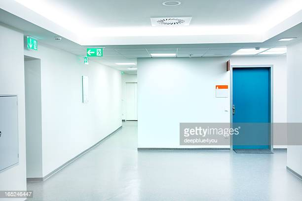 Corredor do Hospital vazio branco com a porta azul