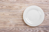 Empty white plate on wooden table. Template for your design.