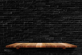Empty wood board shelf at black brick wall background,Mock up for display or montage of product or design.