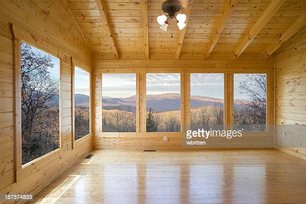 Empty wood room with several windows looking out to mountain