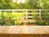 Empty wood table top on blur abstract garden and house background. For montage product display