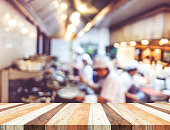 Empty wood table with blur open cooking restaurant background,Mock up Template for montage of your product.