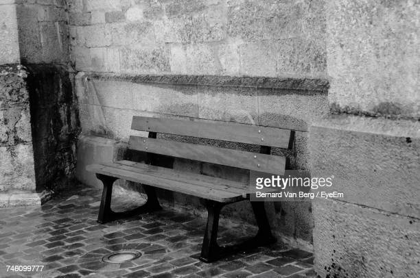 Empty Wooden Bench Against Wall