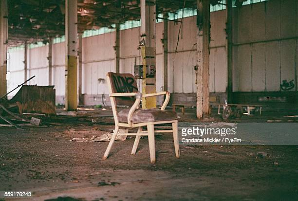Empty Wooden Chair In Abandoned Warehouse