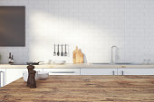Close up of empty wooden kitchen counter on blurry interior background. Copy space, 3D Rendering