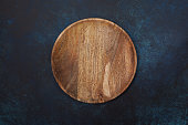 empty wooden plate on a blue background. view from above.