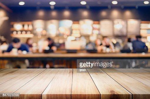 Empty wooden table for present product on coffee shop or soft drink bar blur background with bokeh image. : Stock Photo