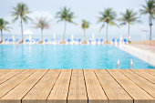 Empty wooden table in front with blurred background of swimming pool at beach,space for montage products