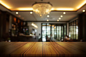 Empty wooden table top with blur coffee shop or restaurant interior background. Abstract background can be used product display.