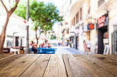 Night view of an empty rustic wooden table in the foreground with defocused lights of a town street café at background ideal for product or food display. Predominant colors are brown and yellow. DSRL