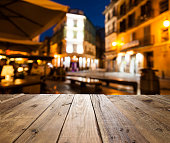 Night view of an empty rustic wooden table in the foreground with defocused lights of a street café at background ideal for product or food display. Predominant colors are brown and yellow. DSRL outdo