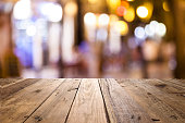 Night view of an empty rustic wooden table in the foreground with defocused street lights at background ideal for product or food display. Predominant colors are brown and yellow. DSRL outdoors photo