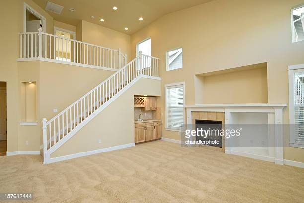 Empty yellow living room with a staircase to a second level