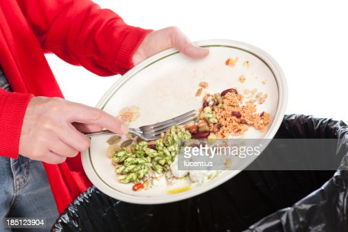 Emptying food leftovers into rubbish bin