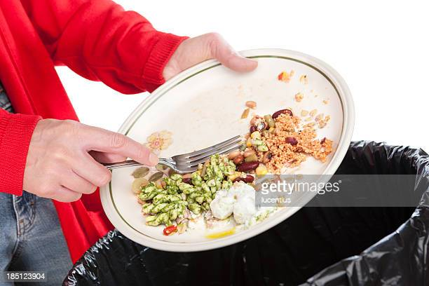 Emptying food leftovers into rubbish bin