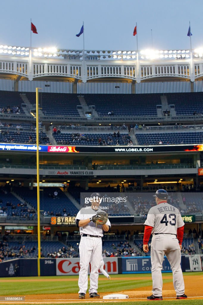 Empyt seats are seen as Lyle Overbay #55 of the New York Yankees talks with first base coach Arnie Beyeler #43 of the Boston Red Sox prior to the first pitch of their game at Yankee Stadium on April 4, 2013 in the Bronx borough of New York City. The Yankees defeated the Red Sox 4-2.