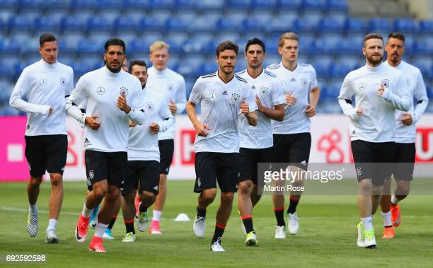 Emre Can Jonas Hector and Shkodran Mustafi jog with team mates during a Germany training session ahead of their international friendly match against...